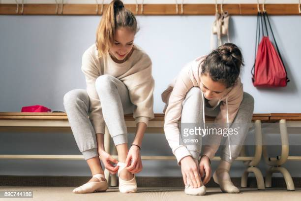 two teenage girls dressing for ballet lesson
