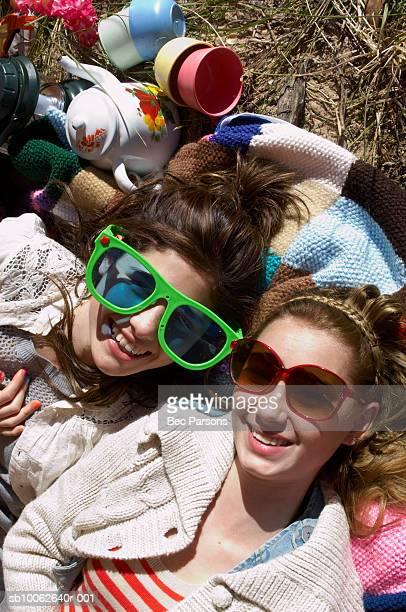 Two teenage girls (16-17) earring sunglasses, lying on blanket outdoors, overhead view