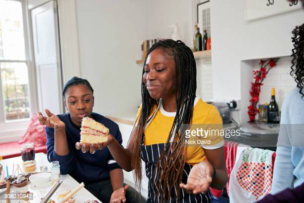 two teenage girls (12-13, 14-15) eating cake in kitchen - baked stock pictures, royalty-free photos & images