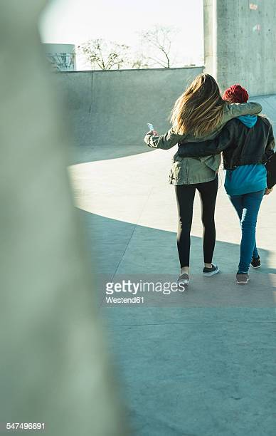 Two teenage girls embracing in skatepark
