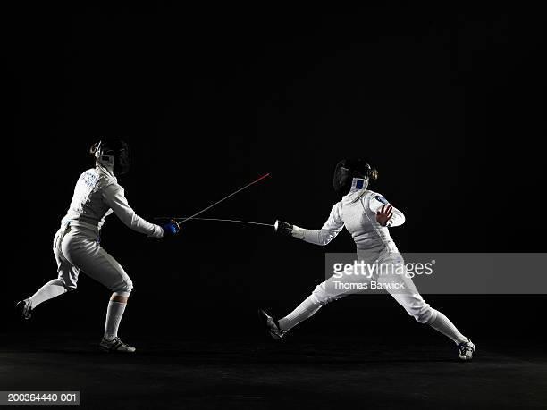 two teenage girls (15-18) fencing, side view - esgrima esporte de combate - fotografias e filmes do acervo
