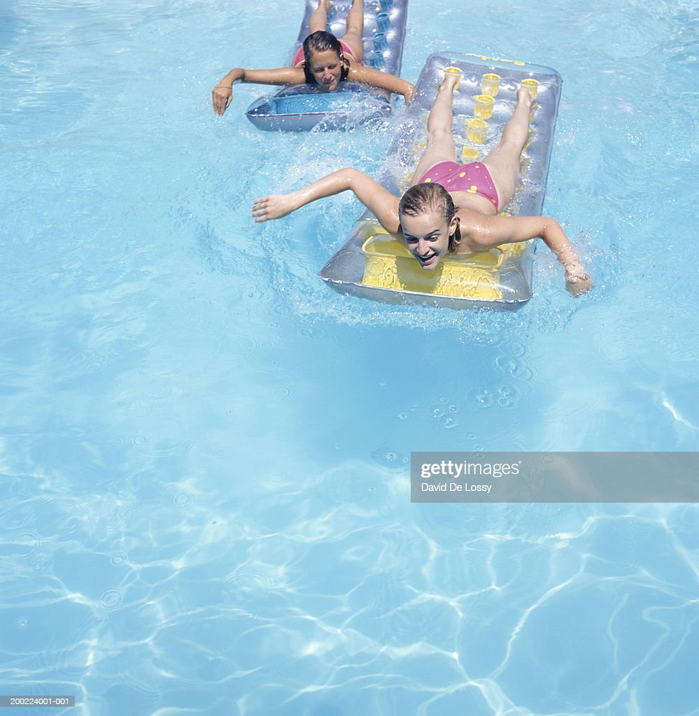 Two teenage girls (16-17) floating face down on airbeds in pool, elevated view : Stock Photo