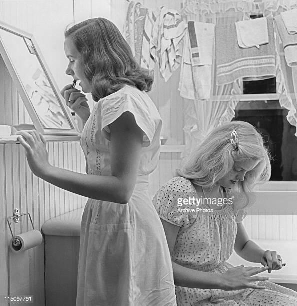 Two teenage girls getting ready in a bathroom circa 1960