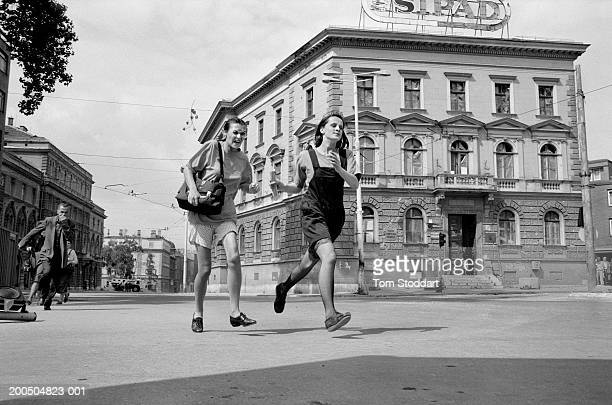 Two teenage girls grimace with fear as they sprint across an intersection on Sniper Alley. During the 47 months between the spring of 1992 and...