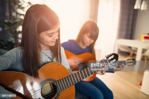 Two teenage girls having fun playing guitars together