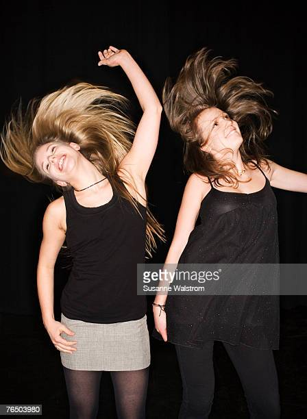 Two teenage girls head banging on a dance floor Sweden.