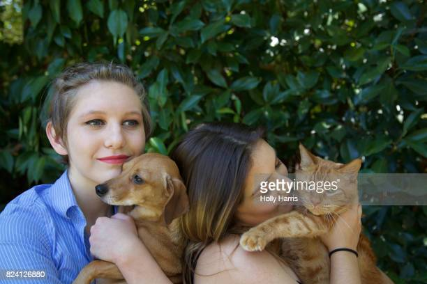 Two teenage girls holding a Dachshund dog and an orange Tabby cat