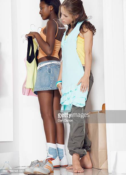 Two teenage girls (13-15) holding clothes on hangers in change room