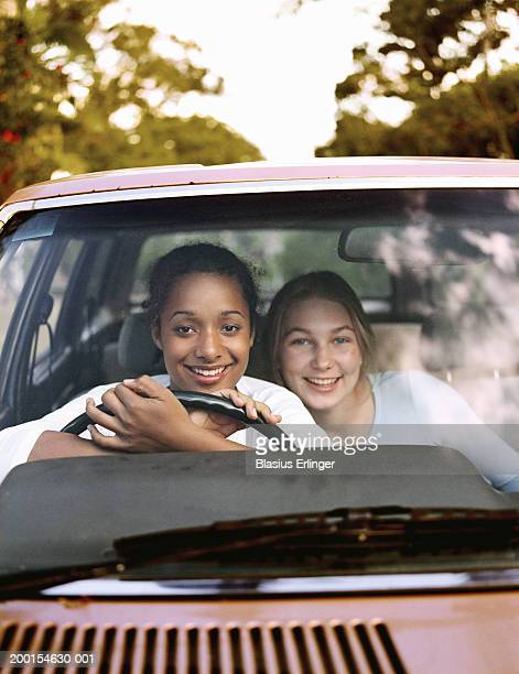 two teenage girls (15-17) in car, smiling, portrait - blasius erlinger stock pictures, royalty-free photos & images