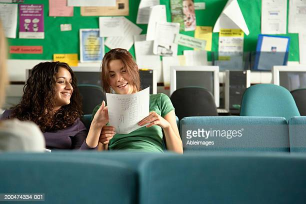 'Two teenage girls (16-18) in common room looking at paper, smiling'
