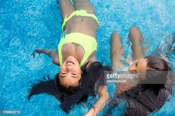 """two teenage girls in pool playing mermaids. - """"martine doucet"""" or martinedoucet stock pictures, royalty-free photos & images"""