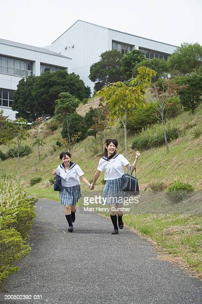 two teenage girls (14-16) in school uniforms running down footpath - ユニフォーム ストックフォトと画像