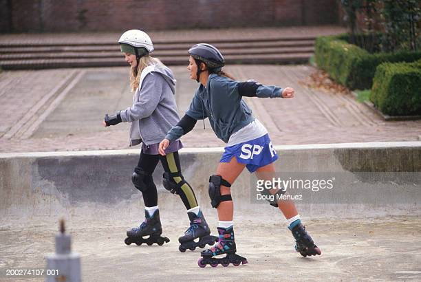 Two teenage girls (14-15) inline skating in park