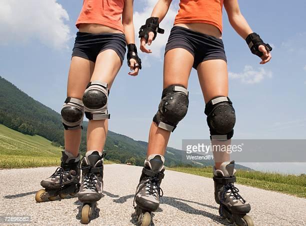 two teenage girls (13-15) inline skating, low section - caneleira roupa desportiva de proteção imagens e fotografias de stock