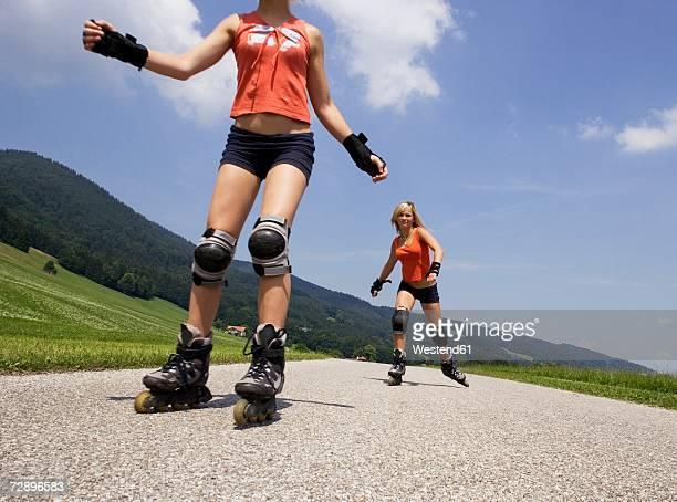 two teenage girls (13-15) inline skating - caneleira roupa desportiva de proteção imagens e fotografias de stock