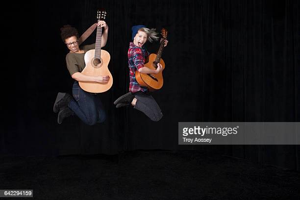 two teenage girls jumping holding guitars. - guitare classique photos et images de collection