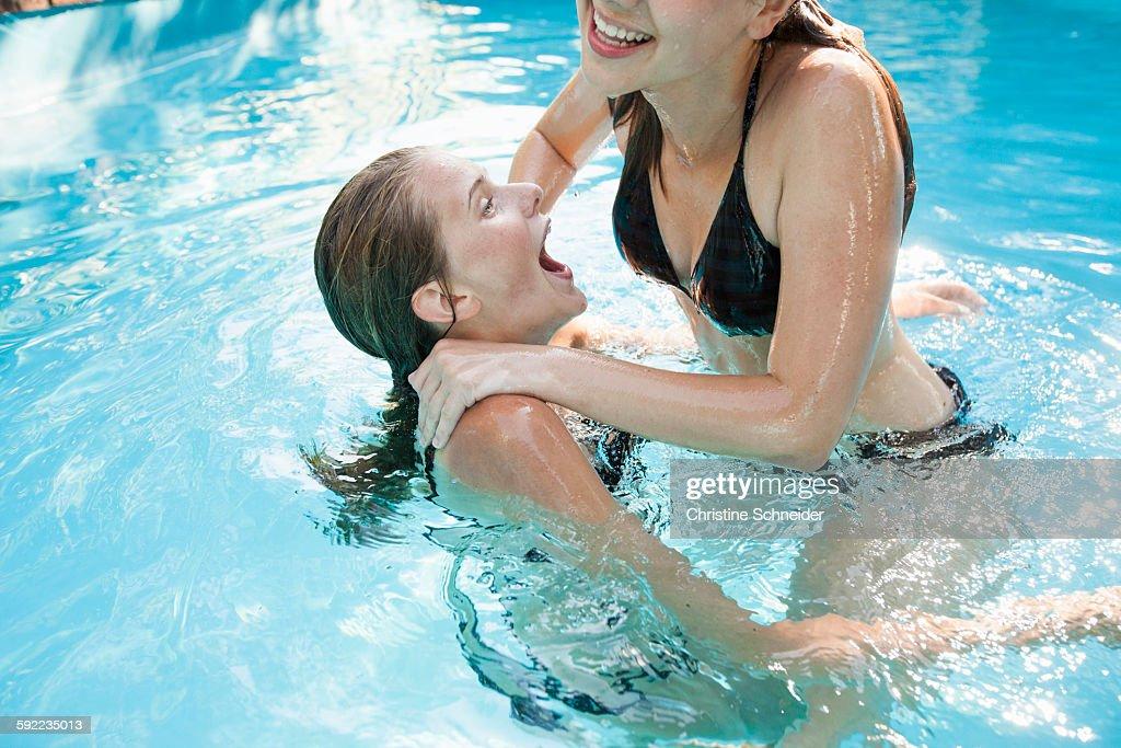 Swimming Pool Identification : Two teenage girls jumping in swimming pool photo getty