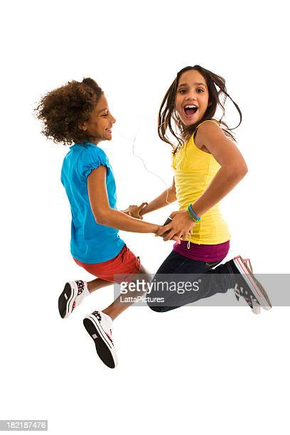 Two teenage girls jumping mid air making a face