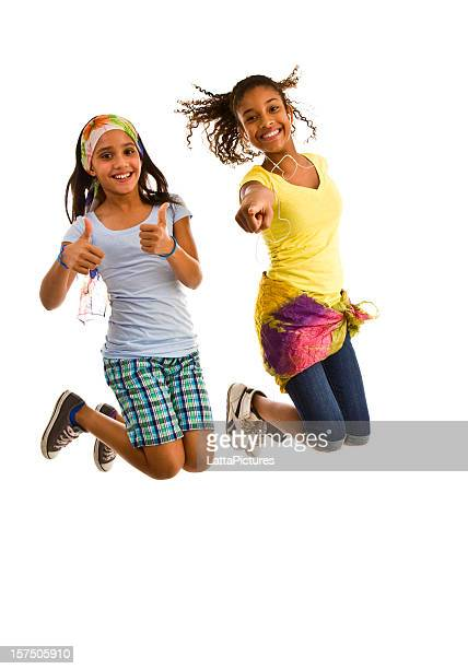 Two teenage girls jumping mid-air with thumbs up