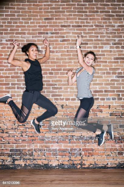 Two teenage girls jumping near brick wall