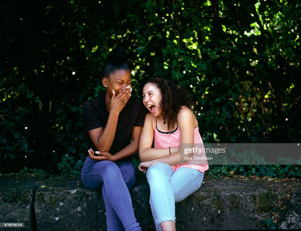 Two teenage girls laughing together in a park