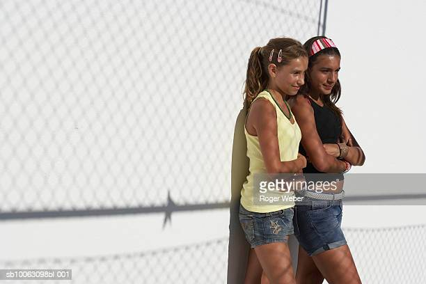 Two teenage girls (12-14) leaning on wall outdoors, arms crossed