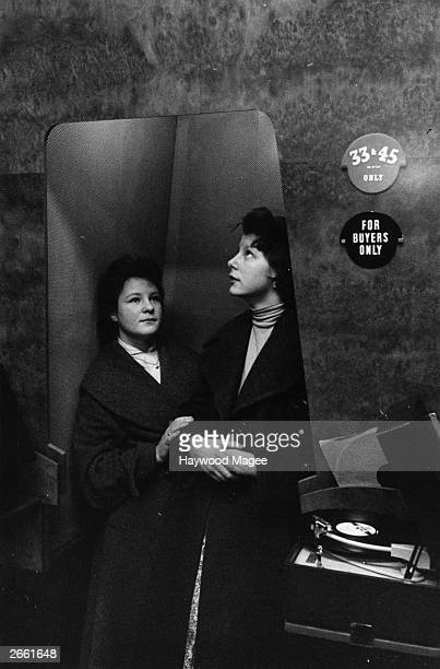 Two teenage girls listening to a record in a booth at a London record store 5th October 1956 Original Publication Picture Post 8710 Dean Worship In...