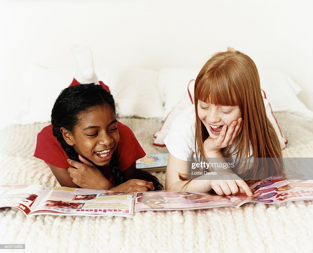 Two Teenage Girls Lying on Bed Reading Magazines, One Girl Pointing at an Image : Stock Photo