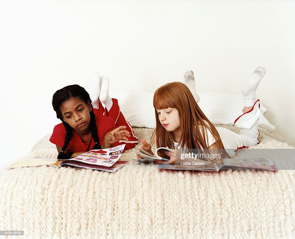 Two Teenage Girls Lying on Bed Reading Magazines : Stock Photo