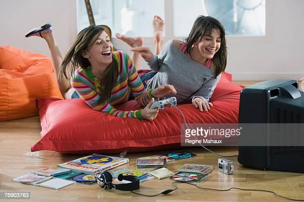 Two teenage girls (14-15, 16-17) lying on mattress, playing video games