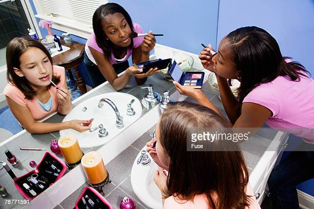 two teenage girls making up in bathroom - vanity mirror stock photos and pictures