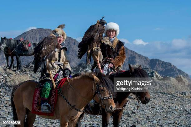 Two teenage girls of Kazakh Eagle hunters and their Golden eagles on horseback on the way to the Golden Eagle Festival near the city of Ulgii in the...
