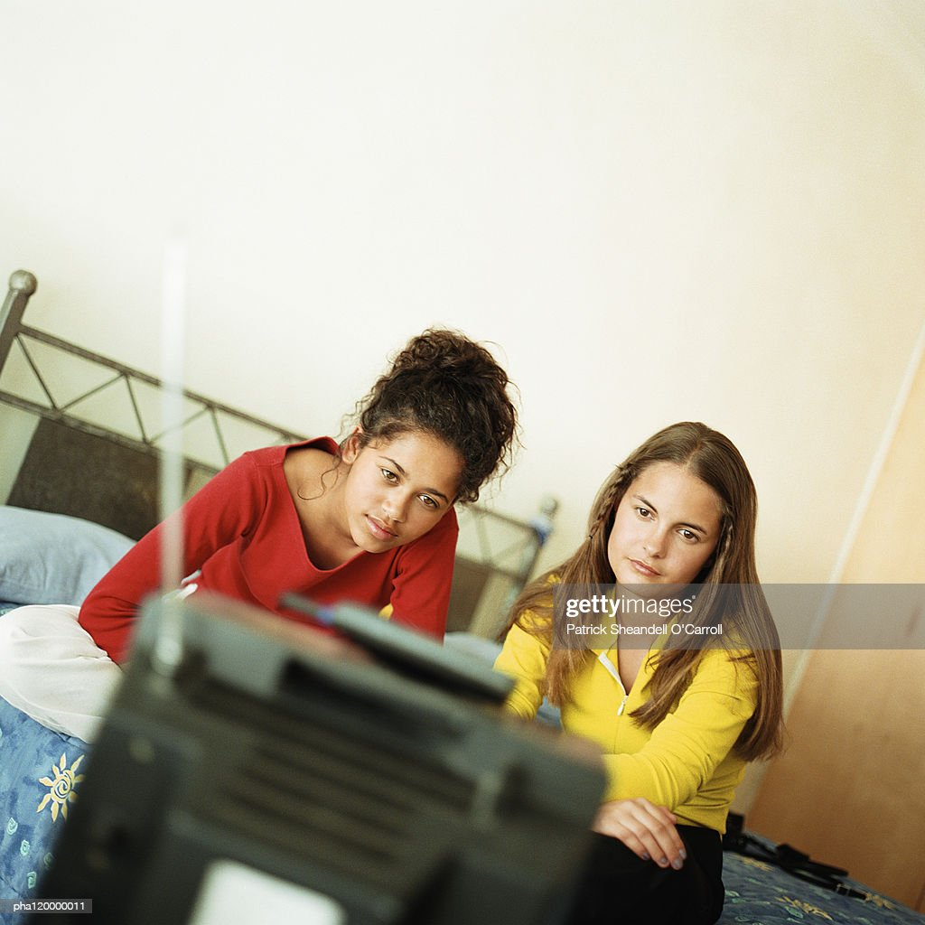 Two teenage girls on bed watching television : Stockfoto