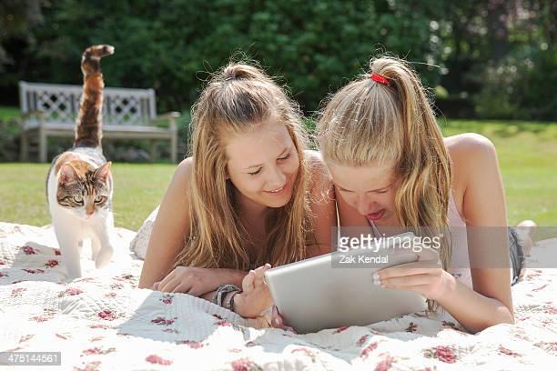 Two teenage girls on picnic blanket looking at digital tablet