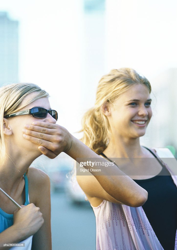 Two teenage girls, one covering the other's mouth : Stockfoto