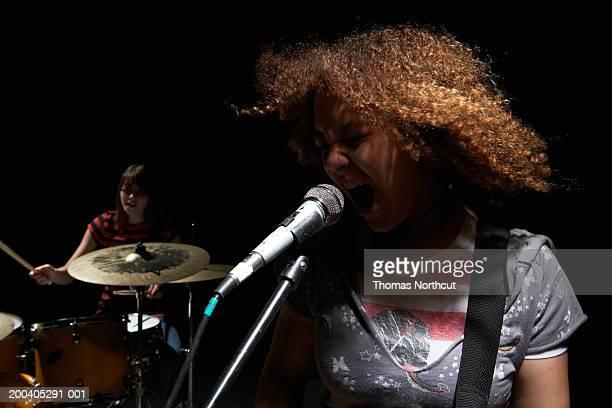 two teenage girls (14-16), one girl playing drums, one girl singing - sångare artist bildbanksfoton och bilder