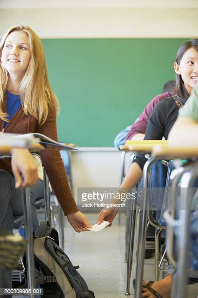 Two teenage girls passing notes in a classroom