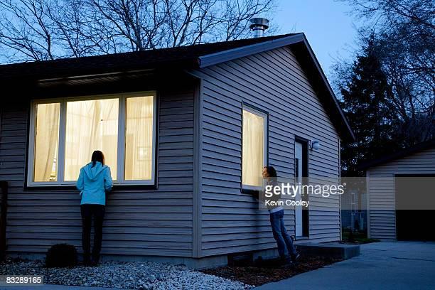 Two teenage girls peering through windows at night