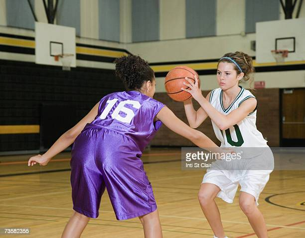 Two teenage girls (14-17) playing basketball