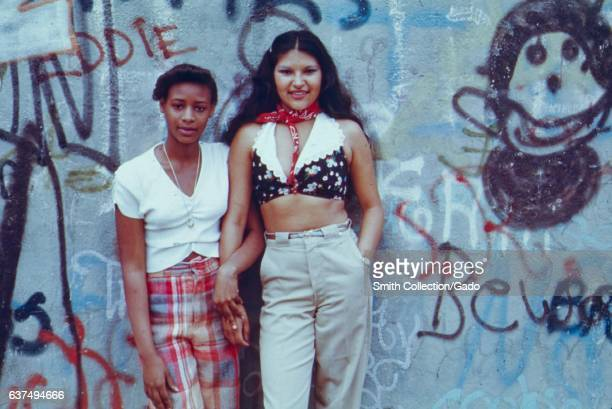 Two teenage girls posing in front of a wall of graffiti in Lynch Park Brooklyn New York City New York June 1974 Image courtesy National Archives