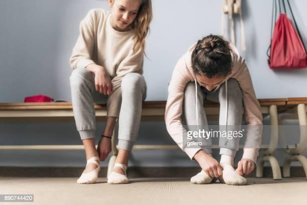 zwei Mädchen im Teenageralter anziehen Schuhe für Ballett-Unterricht