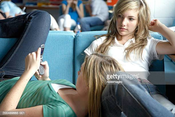 Two teenage girls (14-16) relaxing in college common room
