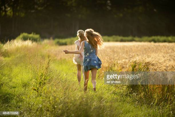 Two teenage girls running on meadow at barley field