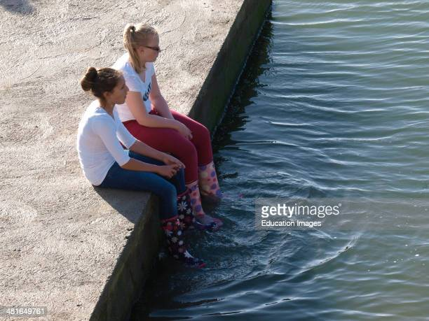 Two teenage girls sat on the edge of sea pool dangling feet in the water Bude Cornwall UK