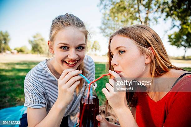 Two teenage girls sharing an ice tea in park