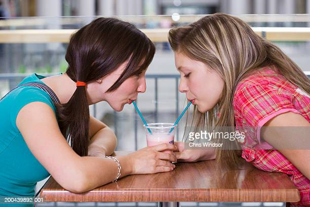 Two teenage girls (15-17) sharing fresh juice at cafe table, profile