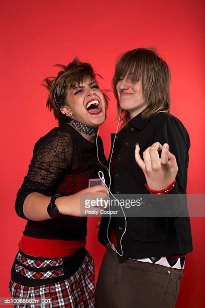 Two teenage girls (16-17) sharing mp3 player, studio shot
