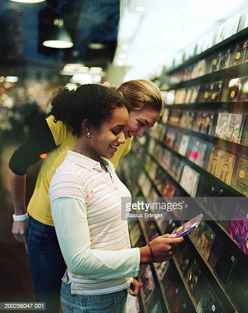 two teenage girls (15-17) shopping in music store (focus on girls) - blasius erlinger stock pictures, royalty-free photos & images