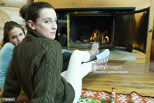 two teenage girls sitting by fireplace, smiling at camera - teen pantyhose stock photos and pictures