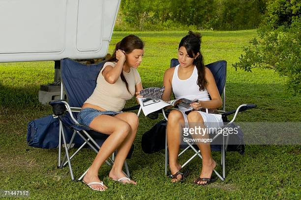 Two teenage girls sitting in armchairs and reading a magazine
